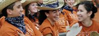 Group of students celebrating wearing University of Texas t-shirts and laughing.